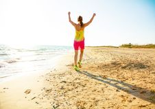 Modern woman in colorful dress on beach in evening rejoicing Royalty Free Stock Image
