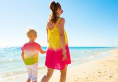 Trendy mother and child on seacoast walking. Colorful and wonderfully cheerful mood. Seen from behind trendy mother and child in colorful clothes on the seacoast Royalty Free Stock Photos