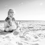 Smiling modern child in colorful shirt on beach blowing bubbles. Colorful and wonderfully cheerful mood. smiling modern child in colorful shirt on the beach stock images