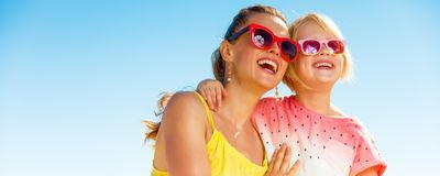 Smiling mother and daughter on seacoast looking into distance. Colorful and wonderfully cheerful mood. smiling modern mother and daughter in colorful clothes on stock image