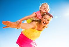 Smiling modern mother and daughter on seashore having fun time. Colorful and wonderfully cheerful mood. smiling modern mother and daughter in colorful clothes on stock images