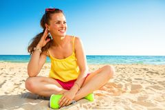 Smiling trendy woman on seashore looking at copy space Royalty Free Stock Images