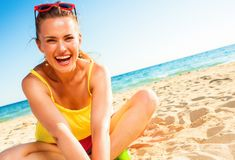 Smiling trendy woman in colorful dress sitting on beach royalty free stock photos