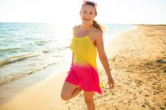 Smiling young woman on seacoast in evening having fun time. Colorful and wonderfully cheerful mood. smiling young woman in colorful dress on the seacoast in the stock photography