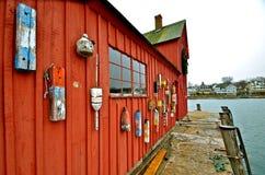 Colorful wood buoys hang on shack stock image