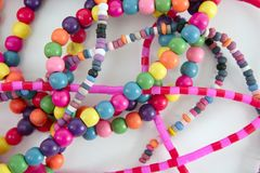 Colorful wood necklaces mess over white Royalty Free Stock Photography