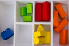 Colorful wood toy building blocks in white tray. Play and learn concept stock photography