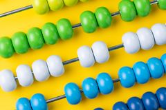 Colorful wooden abacus beads on yellow background, business fina Royalty Free Stock Images