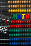 Colorful Wooden Abacus and Calculator. Wooden and colorful abacus and a modern calculator on a blackboard with a simple mathematical addition and text Math ( Royalty Free Stock Image