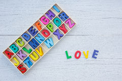 Colorful wooden alphabet in square box and LOVE word. Top view o Stock Images