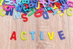 Colorful wooden alphabet and word ACTIVE. Top view on grey woo. Den background Royalty Free Stock Images