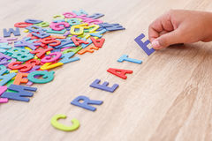 Colorful wooden alphabet and word CREATE, Hand sort on E. Top. View on grey wooden table background Stock Photo