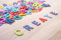 Colorful wooden alphabet and word CREATE. Top view on grey woo. Den table background Royalty Free Stock Photos