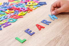 Colorful wooden alphabet and word LEARN, Hand sort on N. Top v. Iew on grey wooden table background Stock Photography