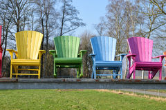 Colorful wooden armchairs on metal structure Stock Images
