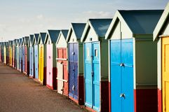 Colorful Wooden Beach Huts. A long row of colorful wooden beach huts on the British coast stock image
