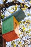 Colorful wooden birdhouse on tree. Design of nesting box. Bird shelter in spring forest. Handmade bird house. Wooden firds feeder in garden stock images