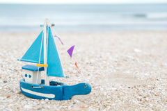 Colorful wooden boat figure on the beach in the evening Stock Image