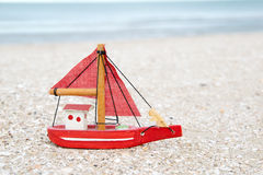 Colorful wooden boat figure on the beach in the evening Stock Photos