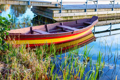 Colorful wooden boat at the riverbank Stock Photos