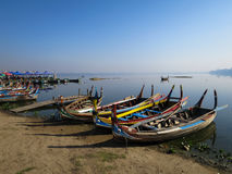 Colorful wooden boats on bank of peaceful still water lake with Royalty Free Stock Image