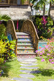Colorful wooden bridge in a tropical garden next to the swimming pool . Bali, Indonesia Stock Photo