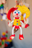 Colorful wooden buffoon figure hanging on the spring Stock Photo