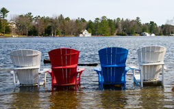 Colorful wooden chairs in a lake Royalty Free Stock Photos