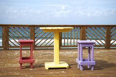 Colorful wooden chairs and table in a tropical environment Royalty Free Stock Photography