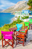 Colorful wooden chairs with view on sea, Greece royalty free stock photo