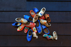Colorful wooden clogs on wooden panels Royalty Free Stock Images