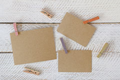 Colorful wooden clothespin clipping pieces of blank brown paper Royalty Free Stock Photos