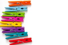 Colorful wooden clothespins on white background with copy space/diversity concept stock photography