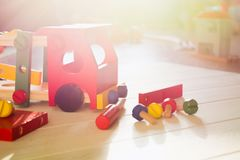 Colorful wooden constructor with details of car, screwdriver and screws. Early education. Preschool skills concept. Sunlight background royalty free stock photo