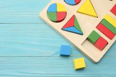 Colorful wooden cubes on blue wooden background. Top view. Toys in the table stock photo
