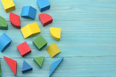 Colorful wooden cubes on blue wooden background. Top view. Toys in the table Stock Photos