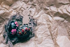 Colorful wooden easter eggs and wooden fanny rabbit on a craft paper background. Toned royalty free stock photo