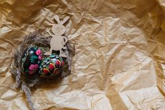 Colorful wooden easter eggs and wooden fanny rabbit on a craft paper background. Toned royalty free stock photography