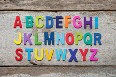 Colorful wooden English alphabet set. On grunge wooden background Royalty Free Stock Image