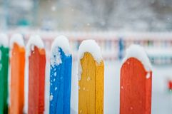 Colorful wooden fence under snow. Blue, red, yellow, orange fence parts under snow. Closeup view Royalty Free Stock Photo