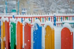 Colorful wooden fence under snow. Blue, red, yellow, orange fence parts under snow Stock Image