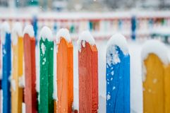 Colorful wooden fence under snow. Blue, red, yellow, orange fence parts under snow Stock Photo