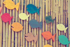 Colorful wooden fishes on the bamboo surface, Royalty Free Stock Photos