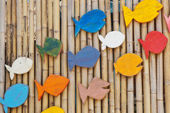 Colorful wooden fishes on the bamboo surface, Stock Images