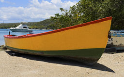 Colorful Wooden Fishing Boat. A brightly colored wooden fishing boat on a sandy beach located in a tranquil harbor setting in the Caribbean Royalty Free Stock Photo