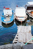 Colorful wooden fishing boats, Turkey. Colorful wooden fishing and pleasure boats moored in small port of Avcilar, district of Istanbul, Turkey. Vertical photo Royalty Free Stock Photography