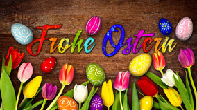 Colorful wooden german happy easter background. Tulips eggs nest basket on rustic old oak wood texture Stock Image