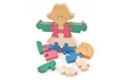 Colorful wooden girl standing on boy puzzle pieces isolated Stock Photos