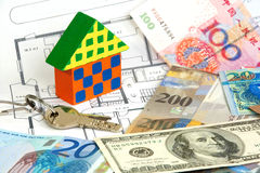 Colorful wooden house and currencies Stock Photos