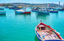 The colorful wooden luzzu boats, Marsaxlokk. The colorful wooden luzzu boats are the pearl of the small fishing village of Marsaxlokk, Malta royalty free stock images